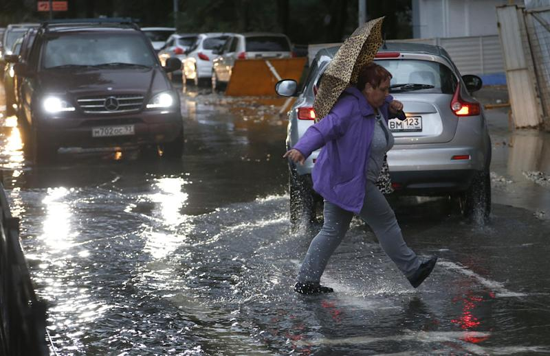 A woman runs across a puddle as the city streets fill with water after heavy rains in Sochi, Russia, Tuesday, Sept. 24, 2013. Many critics still complain about underdeveloped infrastructure in Sochi, where the Olympics will be held in February 2014. (AP Photo/Sergei Grits)