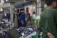 A burqa-clad woman checks footwear displayed on a stall at a market area in Kabul (AFP/BULENT KILIC)