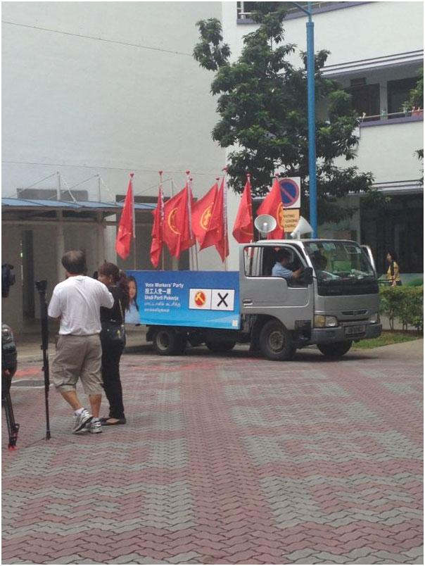 Workers' Party's van for thank you parade rests by Block 113. Supporters gathering and waiting for Lee Li Lian.