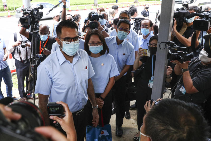 Workers' Party Secretary-General Pritam Singh, left, and Chairman Sylvia Lim, second left, arrive at a nomination center with their team to submit their nomination papers ahead of the general election in Singapore, Tuesday, June 30, 2020. Campaigning has begun for Singapore's general elections, with the opposition hoping to dent the ruling party's supermajority in parliament. (AP Photo/Yong Teck Lim)