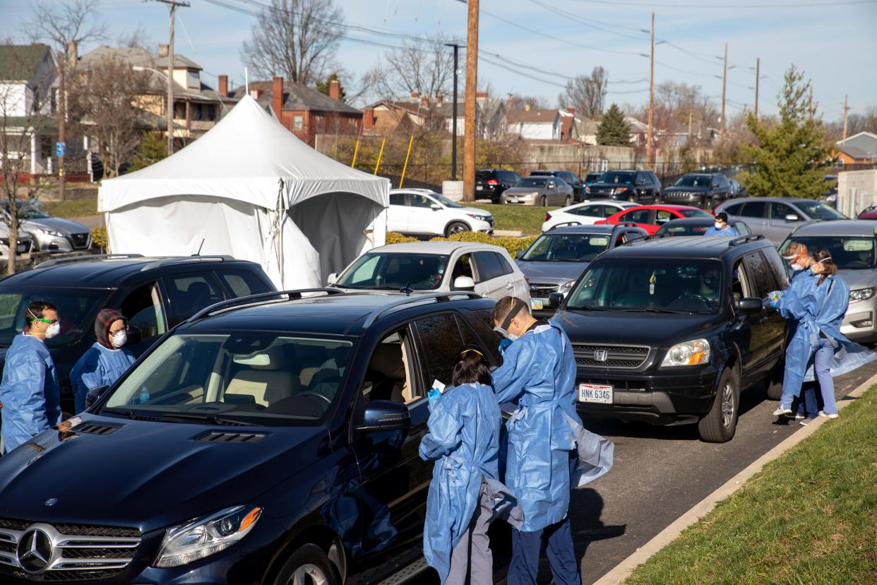 Healthcare workers administer free Covid-19 tests to people in their cars in the parking lot of the Columbus West Family Health and Wellness Center in Columbus, Ohio on November 19, 2020. (Photo by Stephen Zenner / AFP) (Photo by STEPHEN ZENNER/AFP via Getty Images)