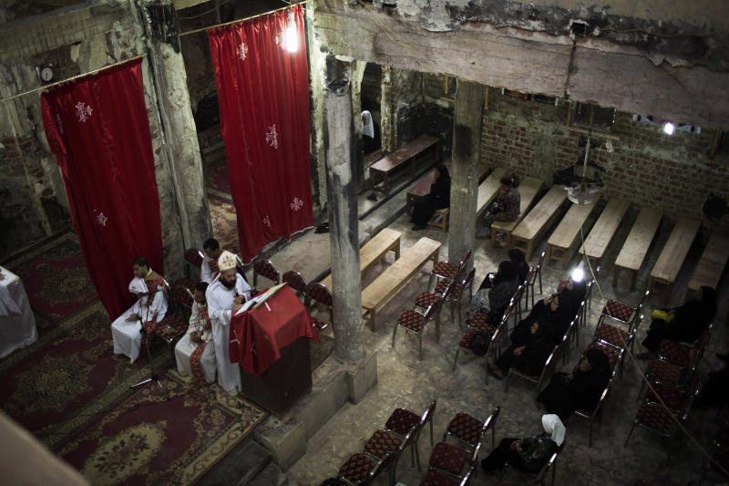 In this Thursday, Oct. 2, 2013 photo, Father Boutros gives the homily to his parishioners at a church burnt by radical Islamists on Aug. 14 in the town of Abanoub, some 400 kilometers (250 miles) south of Cairot. In a show of resilience, some have held Masses and weddings in churches that have been left blackened shells without doors or windows, with only a makeshift altar. Still, priests say, some regular worshippers have stayed away, too hurt to return and see the condition of the churches where they lived out milestones like weddings, baptisms and funerals. (AP Photo/Manu Brabo)