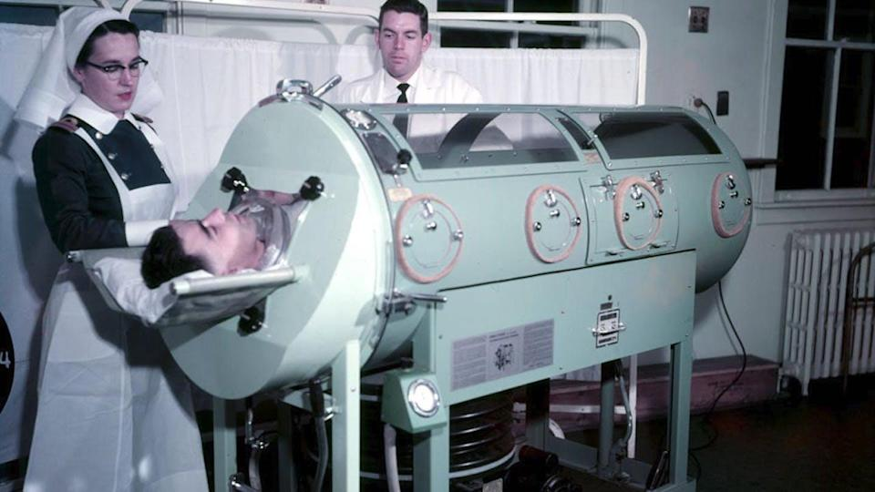 A nurse stands next to man in an iron lung