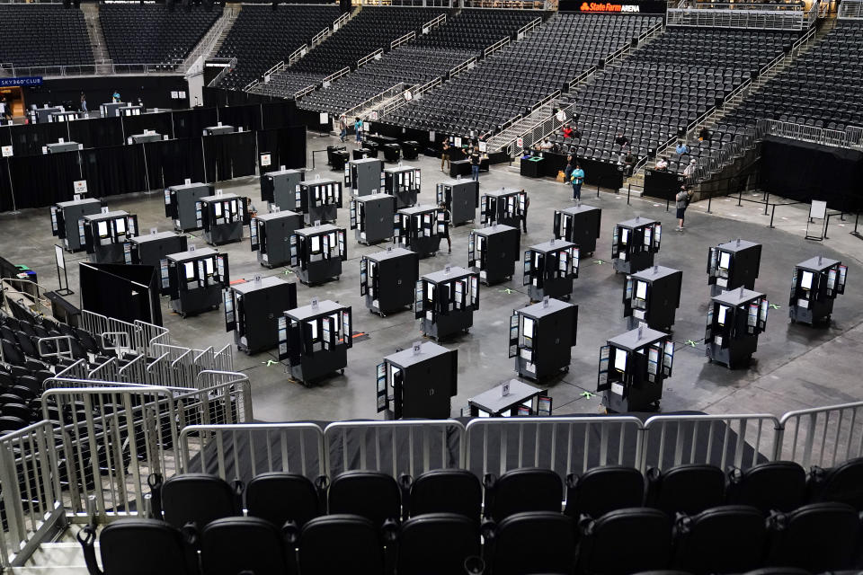 FILE - In this Monday, Oct. 12, 2020 file photo, voting machines fill the floor for early voting at the State Farm Arena in Atlanta. A record-setting 108 million people voted before Election Day, either through early in-person voting or by mailing or dropping off absentee ballots - that represents nearly 70% of all votes cast. (AP Photo/Brynn Anderson)