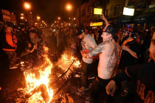 San Francisco Giants fans celebrate next to debris that has been set on fire in the Mission district after the San Francisco Giants beat the Kansas City Royals to win the World Series on Wednesday, Oct. 29, 2014, in San Francisco. (AP Photo/Noah Berger)