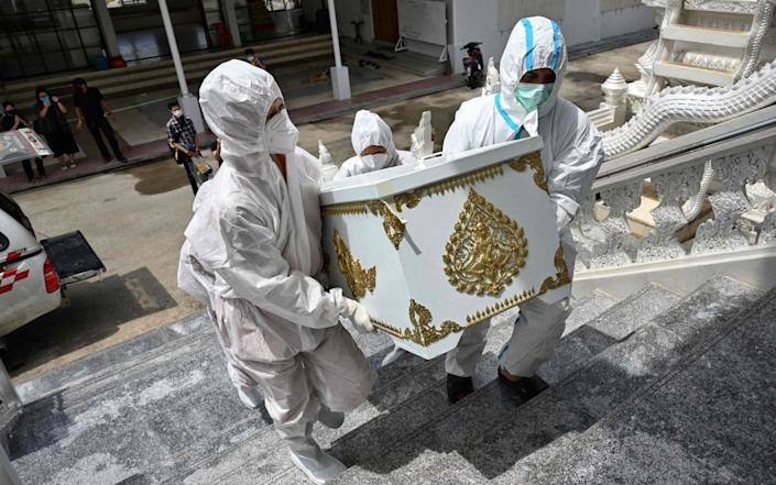 Monks dressed in PPE carry the coffin of Malee Manjeen, 79, who passed away from Covid-19, in Bangkok, Thailand on 30 July 2021 - Lillian Suwanrumpha/AFP