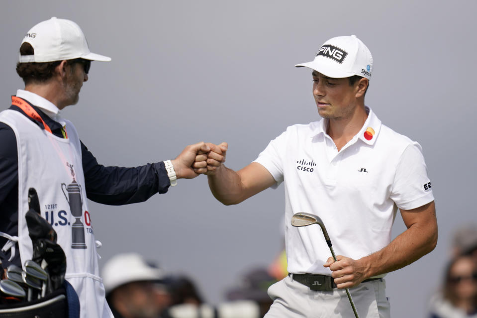 Viktor Hovland, of Norway, right, fist bumps his caddy on the second green during the first round of the U.S. Open Golf Championship, Thursday, June 17, 2021, at Torrey Pines Golf Course in San Diego. (AP Photo/Gregory Bull)