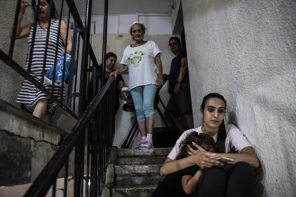 People in Ashdod, Israel take shelter in the stairwell of their apartment building during a siren warning of rockets fired from Gaza to Israel on Tuesday, May 18, 2021. (AP Photo/Heidi Levine)