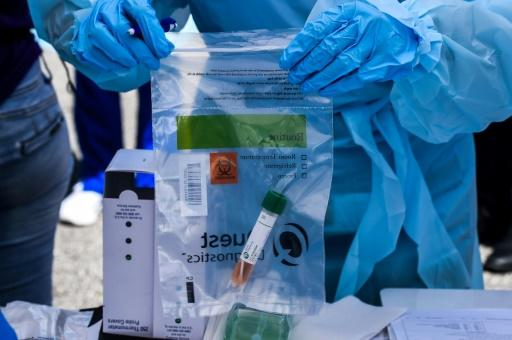 A health worker stores coronavirus test samples at a drive-through clinic in West Palm Beach, Florida