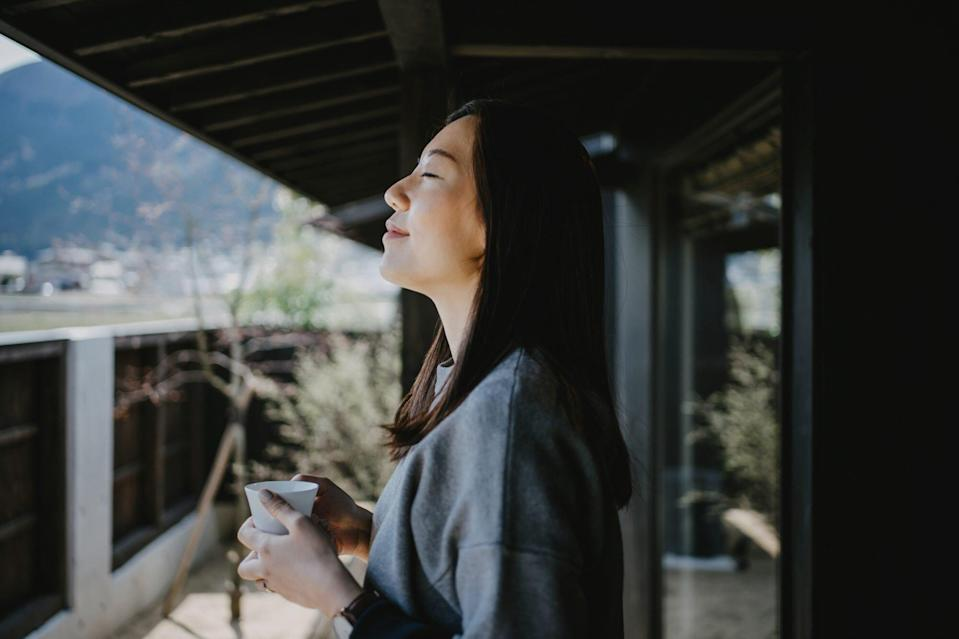 woman drinking coffee and breathing fresh air on balcony in the morning