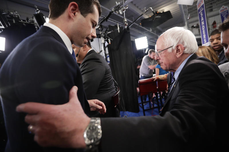 South Bend Mayor Pete Buttigieg, left, and Sen. Bernie Sanders, I-Vt., right, pass as they talk to the media in the spin room following the Democratic presidential primary debate hosted by ABC on the campus of Texas Southern University Thursday, Sept. 12, 2019, in Houston. (AP Photo/Eric Gay)