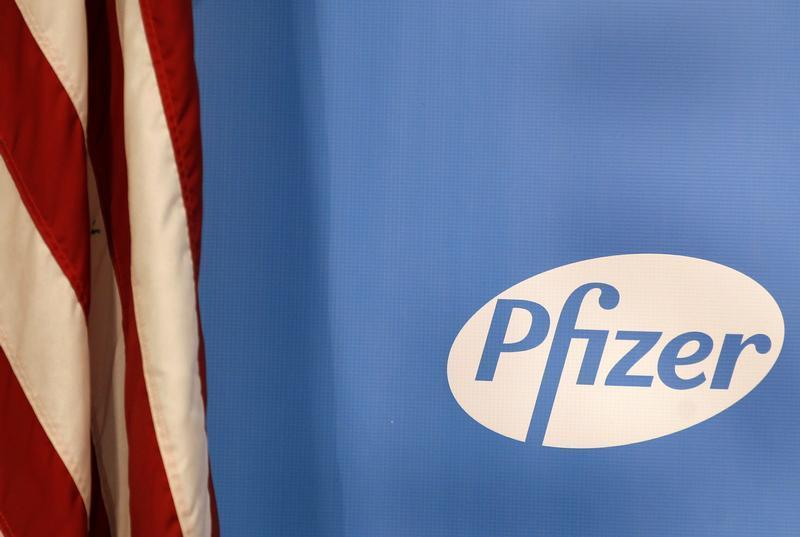 The Pfizer logo is seen next to a U.S. flag in a conference room at their world headquarters in New York