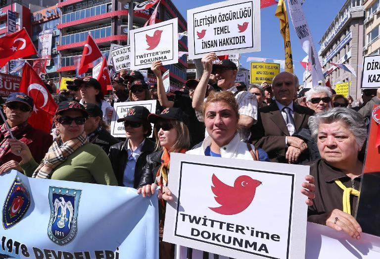 """Protesters hold placards reading """"do not touch my Twitter"""" and """"communication right is a basic human right"""" during a demonstration against a government ban on Twitter in Ankara on March 22, 2014"""