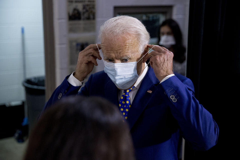 """Democratic presidential candidate former Vice President Joe Biden puts on his mask as he leaves a campaign event at the William """"Hicks"""" Anderson Community Center in Wilmington, Del., Tuesday, July 28, 2020.(AP Photo/Andrew Harnik)"""