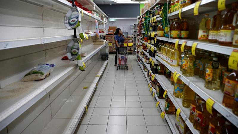 A packet of rice is pictured on an empty shelf as people stock up on food supplies, after Singapore raised coronavirus outbreak alert level to orange, at a supermarket in Singapore February 8, 2020