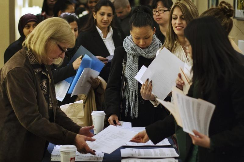 Job seekers adjust their paperwork as they wait in line to attend a job fair in New York