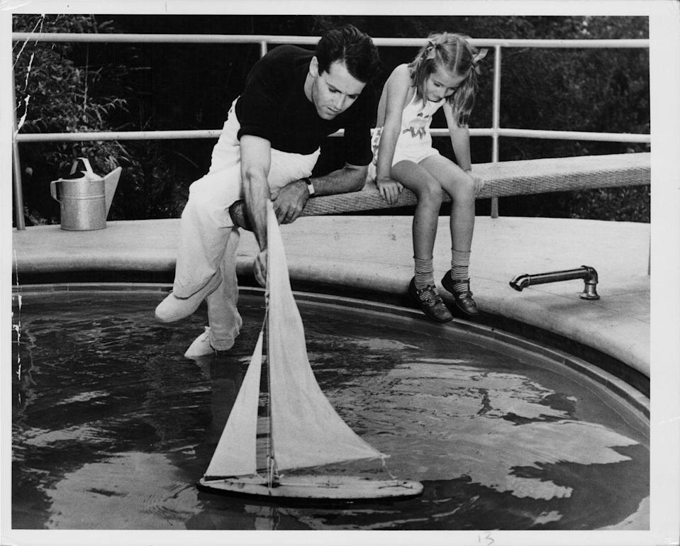 <p>A young Jane Fonda and her father, actor Henry Fonda, play with sailing boat in a swimming pool. </p>