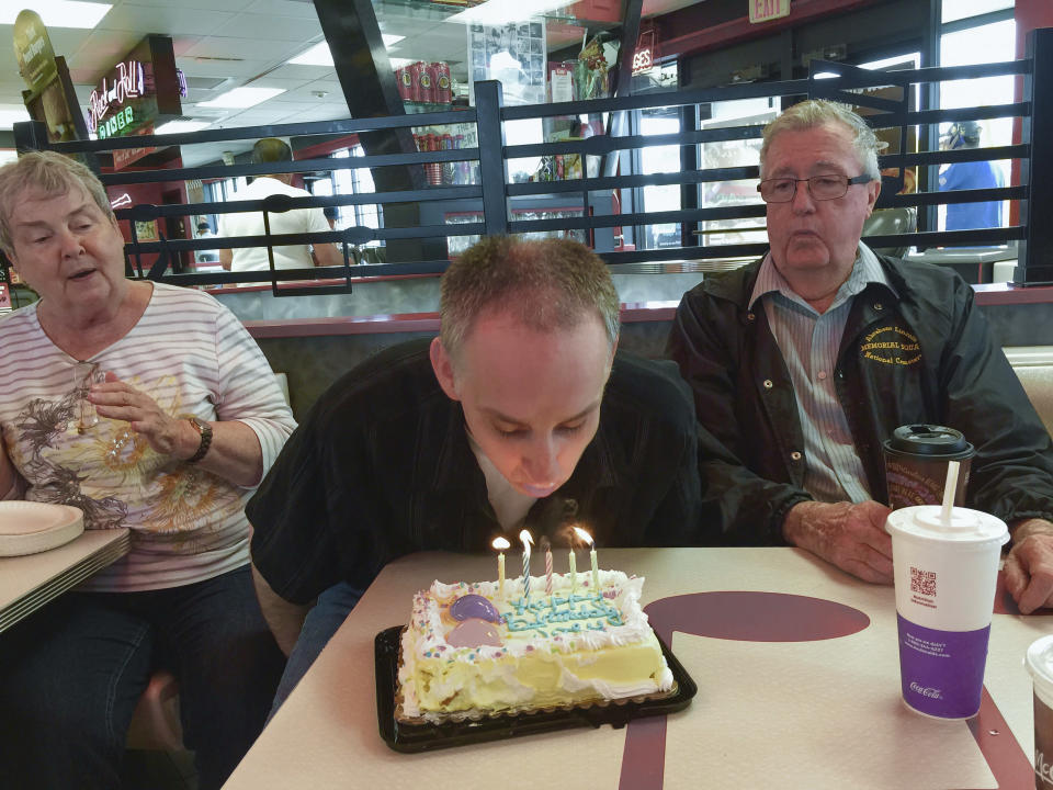 This 2015 photo provided by the family shows Joe Sullivan, of the Chicago-area, and his parents celebrating his birthday at a restaurant. (Family photo via AP)