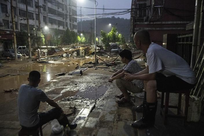 Three people view the flood damage from where they are sitting