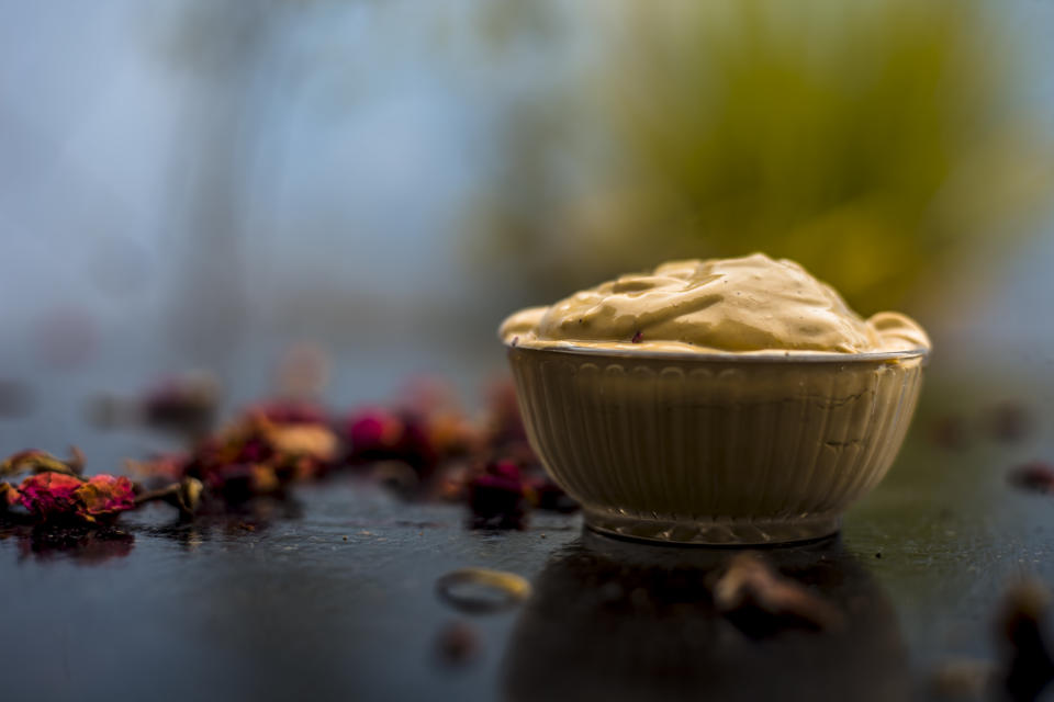 Ubtan/face mask/face pack of Multani mitti or fuller's earth on wooden surface in a glass bowl consisting of Multani mitti and rose water for the remedy or treatment of oily skin.On wooden surface.
