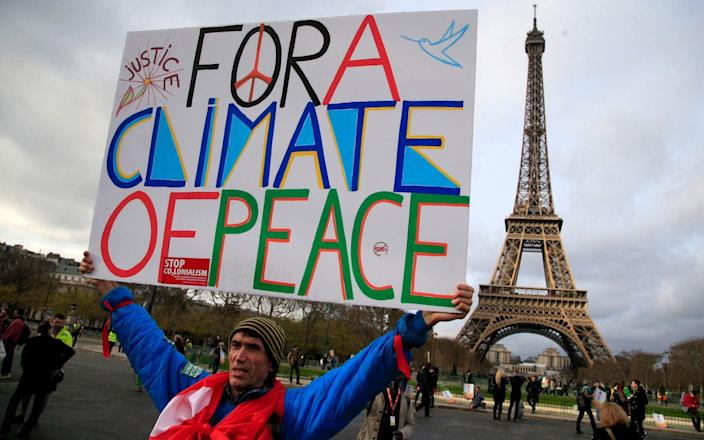 An activist holds a poster during a demonstration near the Eiffel Tower during the Paris COP21 meeting in 2015 - Thibault Camus/AP