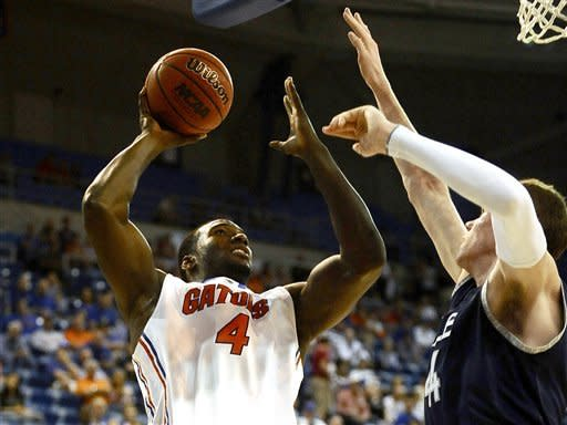 Florida's Patric Young (4) shoots while defended by Yale's Greg Mangano (44) during the first half of an NCAA college basketball game in Gainesville, Fla., Saturday, Dec. 31, 2011. (AP Photo/Phil Sandlin)