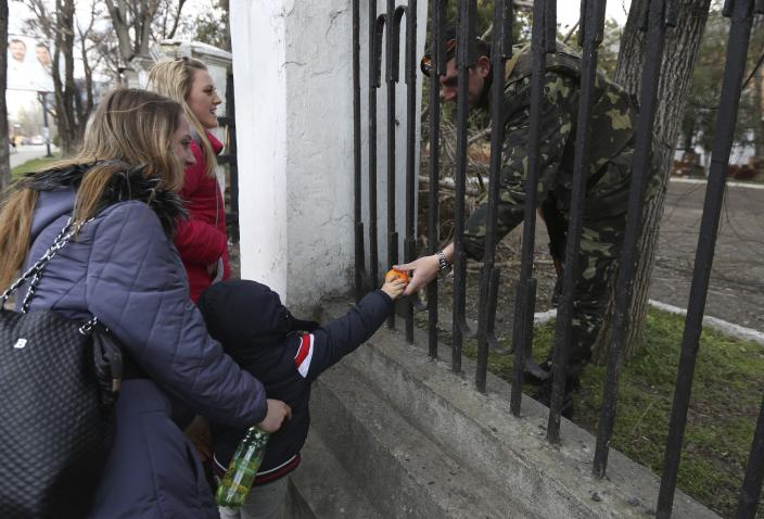 A child gives fruit to a Ukrainian officer at the Ukrainian Military Prosecutor's Office in Simferopol, Crimea, Thursday, March 20, 2014. The lower house of Russian parliament voted Thursday to make Crimea a part of Russia following Sunday's Crimean referendum in which its residents overwhelmingly backed breaking off from Ukraine and joining Russia. (AP Photo/Maxin Vetrov)