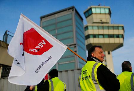 Members of Germany's Verdi union protest with flags at a gate at Tegel airport during a warning strike by ground services, security inspection and check-in staff in Berlin, Germany March 13, 2017. REUTERS/Hannibal Hanschke