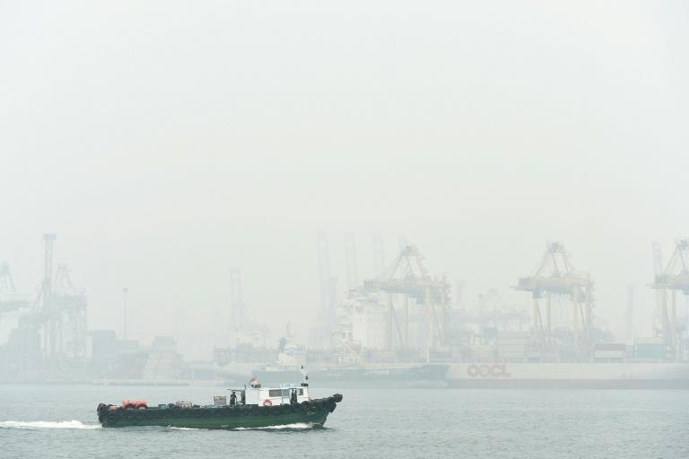 A boat sails past Keppel container port terminal blanketed with thick smog in Singapore on September 24, 2015
