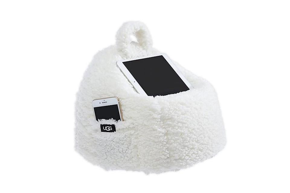 """<p>Everyone needs a place to prop their many, many devices, right? UGG's genius tablet pillow is part comfy spot to rest your head and part storage for your screens, so you don't have to tear apart your bed in the morning. </p> <p><strong>Buy It!</strong> UGG's Classic Sherpa Poof Tablet Pillow, $19.99; <a href=""""https://www.anrdoezrs.net/links/8029122/type/dlg/sid/PEO2020HolidayGiftGuideGiftsEveryTechLoverNeedsThisSeasonawurzburTecGal12384134202011I/https://www.bedbathandbeyond.com/store/product/ugg-reg-classic-sherpa-poof-tablet-pillow-in-snow/5472769"""" rel=""""nofollow noopener"""" target=""""_blank"""" data-ylk=""""slk:bedbathandbeyond.com"""" class=""""link rapid-noclick-resp"""">bedbathandbeyond.com</a></p>"""