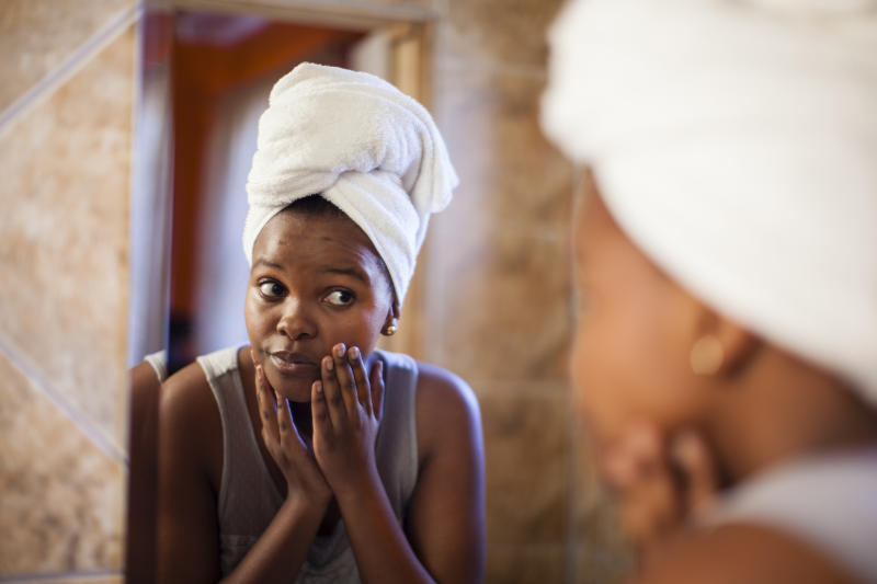 Young woman checks skin in mirror. Image: Getty