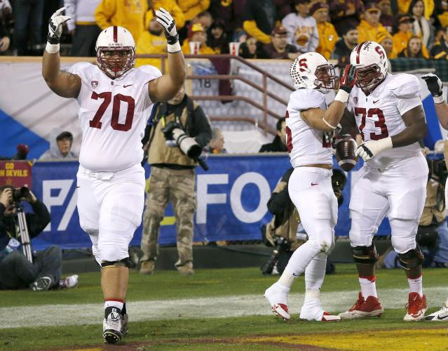Stanford's Andrus Peat (70) and Cameron Fleming (73) celebrate a touchdown run against Arizona State by teammate Tyler Gaffney, second from right, during the first half of the NCAA Pac-12 Championship football game Saturday, Dec. 7, 2013, in Tempe, Ariz. (AP Photo/Ross D. Franklin)