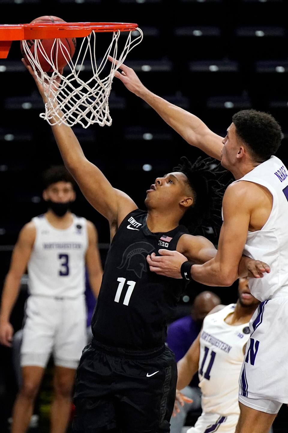 Michigan State guard A.J. Hoggard, left, drives to the basket past Northwestern forward Pete Nance during the first half of an NCAA college basketball game in Evanston, Ill., Sunday, Dec. 20, 2020.