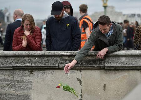 A man drops a flower into the River Thames during an event to mark one week since a man drove his car into pedestrians on Westminster Bridge then stabbed a police officer in London, Britain March 29, 2017. REUTERS/Hannah McKay