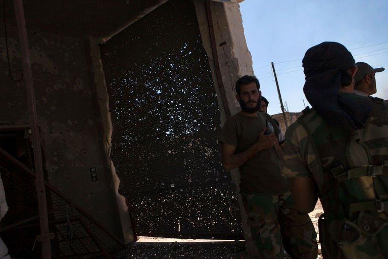 "Rebels stand next to a metal door filled with shrapnel in the village of Al-Rami, near the town of Ariha, in the northwestern Syrian province of Idlib, on June 22, 2013. World powers supporting Syria's rebels decided on Saturday to provide them with urgent military aid so they can counter ""brutal attacks"" by the regime and ""protect the Syrian people."""