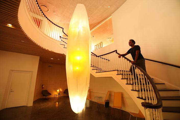 "Rohan Silva stands on the sweeping staircase original designed by Paul R. Williams. The lamp is by artist Doctor Cato. <span class=""copyright"">(Genaro Molina / Los Angeles Times)</span>"
