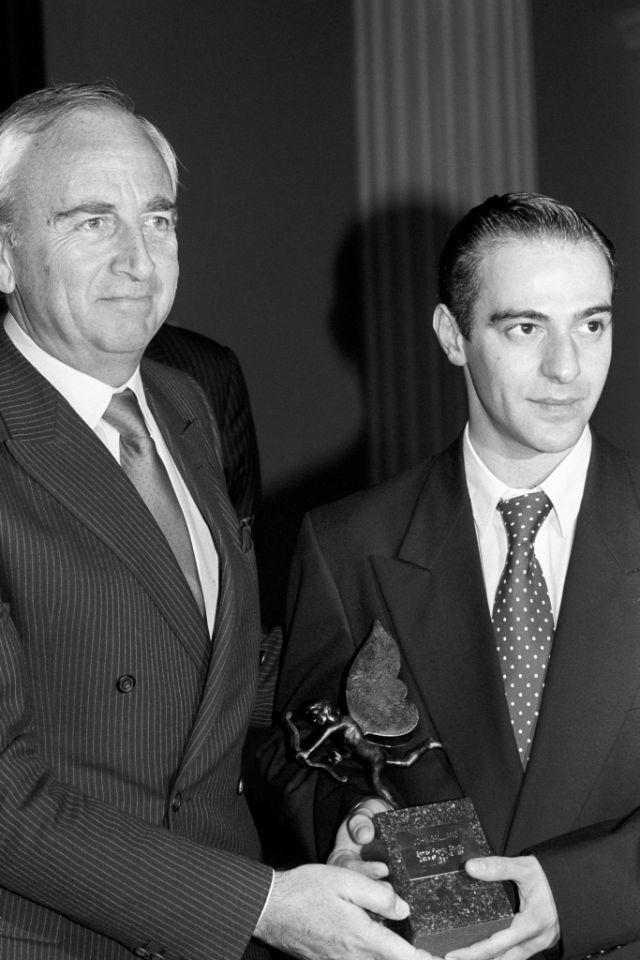<p>John Galliano, 28 ans, reçoit la récompense de créateur de l'année (Designer of the Year Award) du British fashion Council des mains de Lord Young (Trade and Industry secretary) à la fin de la Fashion Week de Londres en 1986. [Photo : PA] </p>
