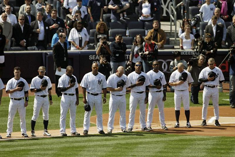 New York Yankees bow their heads during a moment of silence in honor of those killed in Newtown, Conn. before an opening day baseball game against the Boston Red Sox at Yankee Stadium, Monday, April 1, 2013 in New York. (AP Photo/Mark Lennihan)