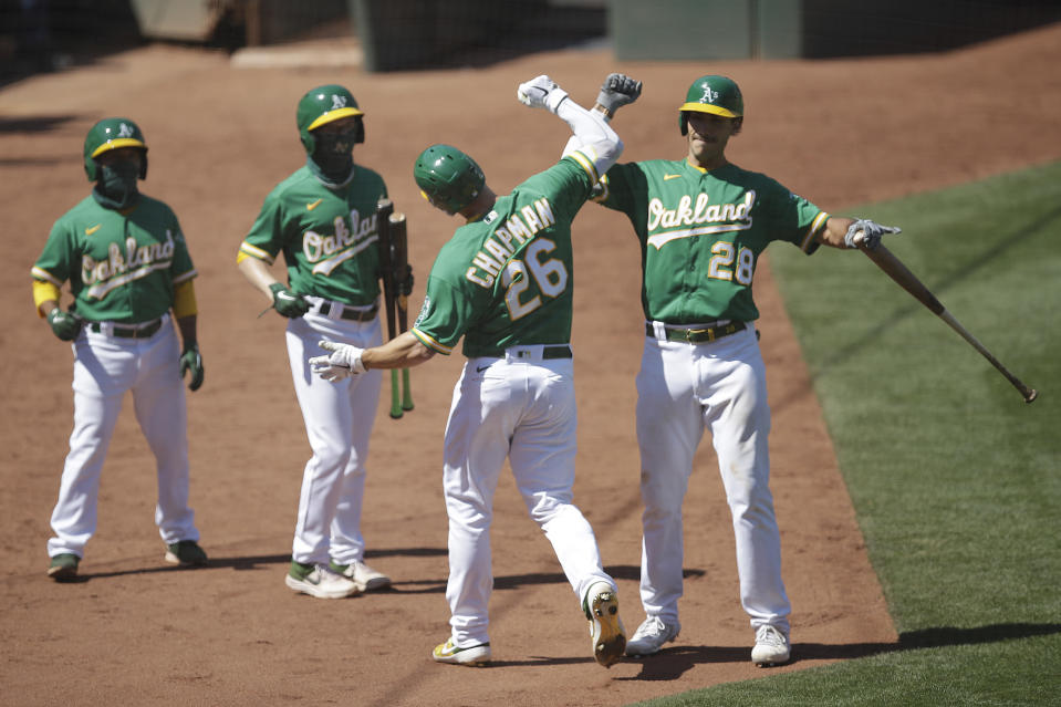 Oakland Athletics' Matt Chapman (26) celebrates with Matt Olson, right, after hitting a home run during the eighth inning of the team's baseball game against the Houston Astros on Saturday, Aug. 8, 2020, in Oakland, Calif. (AP Photo/Ben Margot)