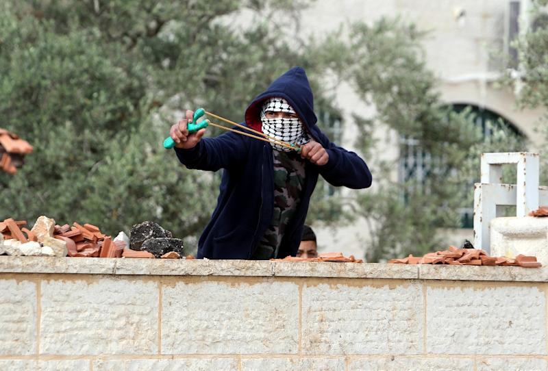 A Palestinian protester from the village of Silwad, north of Ramallah, uses a sling shot to fire stones towards Israeli security forces during clashes following a march in the village on June 5, 2015
