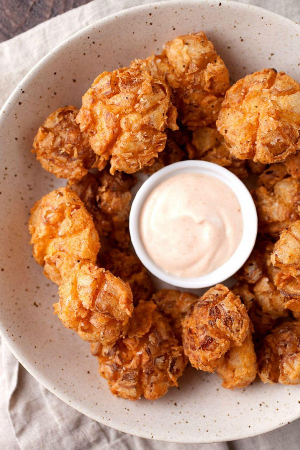 "<p>Battered in rich buttermilk, paprika, cayenne pepper,and garlic powder, these mini blooming onions are the perfect bite-sized party appetizer. </p><p><strong>Get the recipe at <a href=""http://www.macheesmo.com/bite-sized-blooming-onions/"" rel=""nofollow noopener"" target=""_blank"" data-ylk=""slk:Macheesmo"" class=""link rapid-noclick-resp"">Macheesmo</a>.</strong></p>"