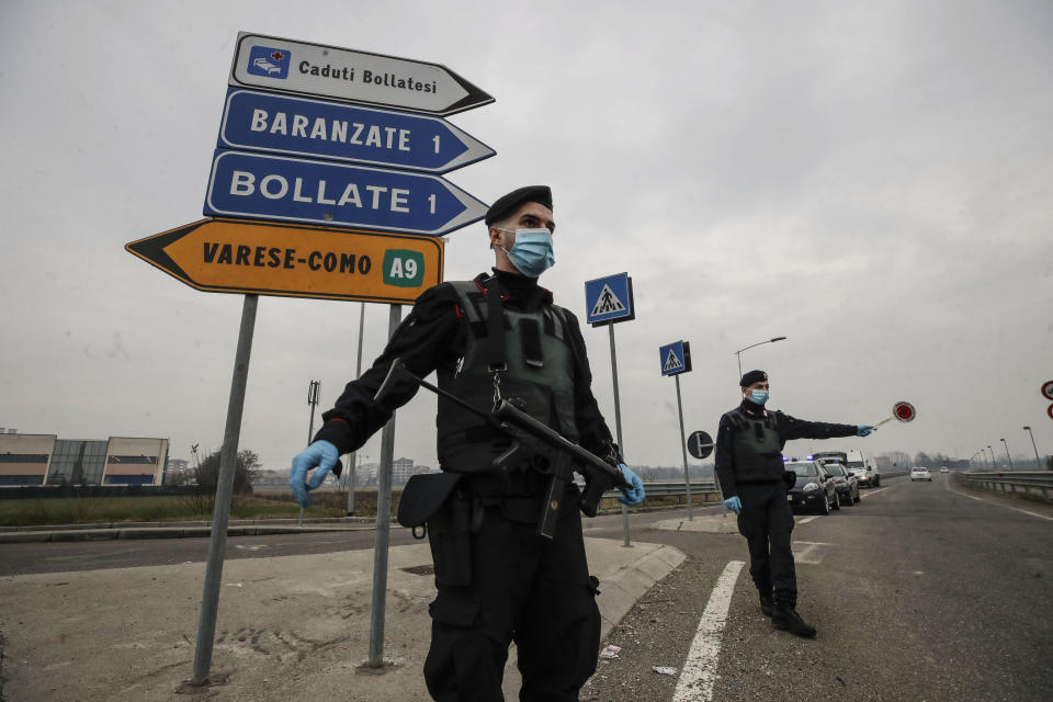 FILE - Carabinieri officers patrol one of the main access road to Bollate, in the outskirts of Milan, Italy. Italy's northern Lombardy region, where Europe's coronavirus outbreak erupted last year, asked the national government Thursday to send more vaccines north to help stem a surge of new cases that are taxing the hospital system in the province of Brescia. Brescia, with a population of around 1.2 million, has seen its daily caseload go from the mid-100s at the start of February to 901 on Wednesday thanks in part to clusters of cases traced to the British variant. (AP Photo/Luca Bruno)