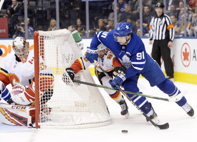 Toronto Maple Leafs center John Tavares (91) looks to wrap the puck around the net as Calgary Flames defenseman Oliver Kylington (58) and goaltender David Rittich (33) defend during the second period of an NHL hockey game Thursday, Jan. 16, 2020, in Toronto. (Nathan Denette/The Canadian Press via AP)