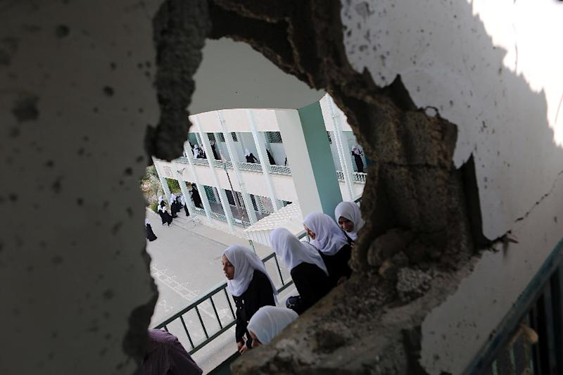 Palestinian girls walk past a hole in a wall at the Suhada Khouza school building, which was damaged during the 50-day war between Israel and Hamas militants in the summer of 2014, in Khan Yunis in the southern Gaza Strip, on September 5, 2015 (AFP Photo/Said Khatib)