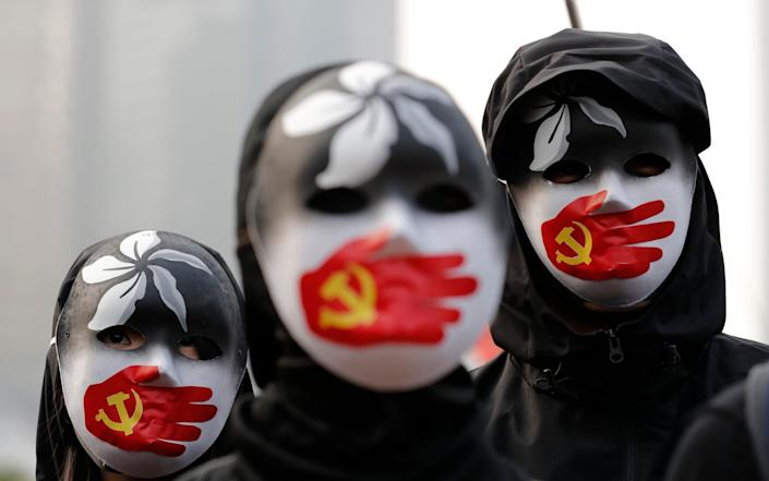 People wearing masks stand during a rally to show support for Uighurs and their fight for human rights in Hong Kong, Sunday, Dec. 22, 2019 - AP