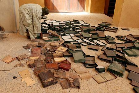 A museum guard works around boxes which held ancient manuscripts which were partially damaged at the Ahmed Baba Institute, or Ahmed Baba Centre for Documentation and Research, in Timbuktu  January 31, 2013. REUTERS/Benoit Tessier/Files