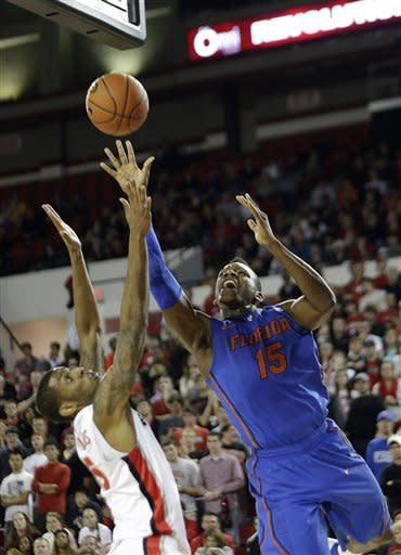 Florida forward Will Yeguete, right, shoots as Georgia forward Donte' Williams, left, defends in the first half of an NCAA college basketball game Wednesday, Jan. 23, 2013, in Athens. Ga. (AP Photo/John Bazemore)