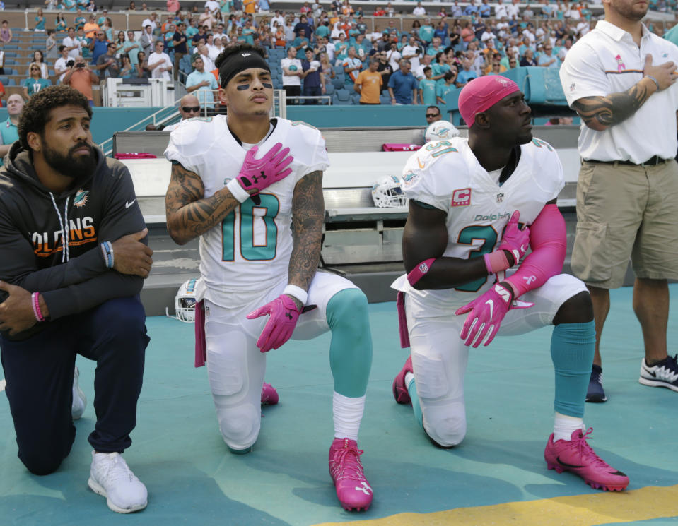 Miami Dolphins wide receiver Kenny Stills (10) and free safety Michael Thomas (31) kneel during the national anthem before a 2016 game. (AP)