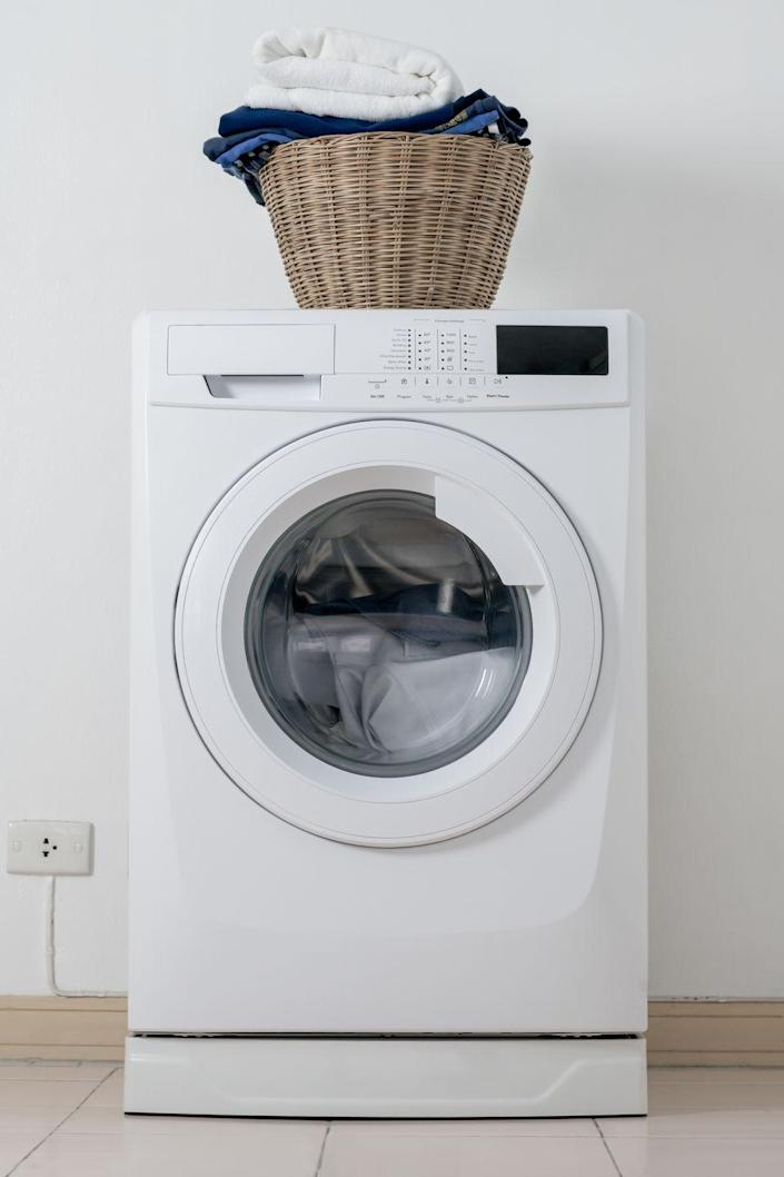 """<p>To clean out the dirt, mold, and other grimy residue that can build up in your washer, <em>Better Homes & Gardens </em>recommends that you <a href=""""https://www.bhg.com/homekeeping/laundry-linens/tips-checklists/how-to-clean-washing-machine/"""" rel=""""nofollow noopener"""" target=""""_blank"""" data-ylk=""""slk:run a hot cycle with vinegar"""" class=""""link rapid-noclick-resp"""">run a hot cycle with vinegar</a>. First, run an empty, regular cycle on hot, using two cups of white vinegar instead of detergent. Then, mix about a quarter cup of vinegar with a quart of warm water and use this mixture — plus a sponge and dedicated toothbrush — to clean the inside of the machine.</p><p>Finally, run one more empty, regular cycle on hot, without detergent or vinegar. If you'd like, you can add half a cup of baking soda to the drum to help clear away buildup loosened from the first cycle. </p>"""