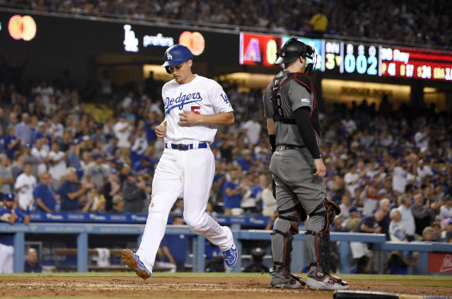 Los Angeles Dodgers' Corey Seager, left, scores on a sacrifice fly by A.J. Pollock as Arizona Diamondbacks catcher Carson Kelly stands at the plate during the third inning of a baseball game Friday, Aug. 9, 2019, in Los Angeles. (AP Photo/Mark J. Terrill)